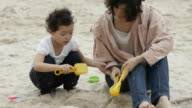 four-years-old asian girl playing with mum on sand, making cake. video