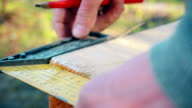 A framing square is used to mark a wooden beam video