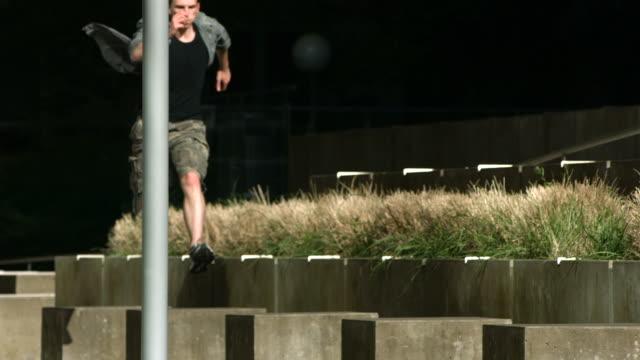 Free runner leaps across concrete blocks, slow motion video
