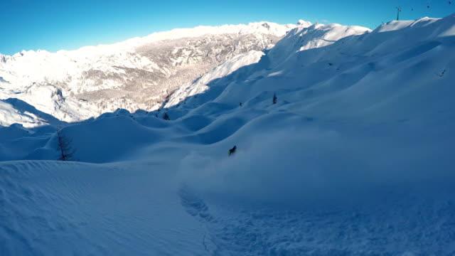 Freeride snowboarder carving in fresh powder snow in snowy mountain ski resort video