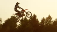 SLOW MOTION: Freestyle motocross biker jumping superman trick over sunset sun video