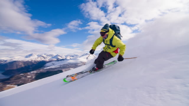 Freestyle skier skiing powder snow with a fjord in background video