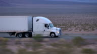 CLOSE UP: Freight semi truck driving and transporting goods on empty highway video