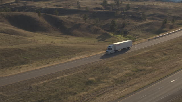 AERIAL: Freight trailer truck transporting goods on road through hilly landscape video