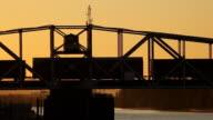 HD freight train crossing bridge at sunset video