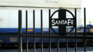 A freight train moves along a railroad track with a Santa Fe Railroad gate sign in the foreground in Arizona. video