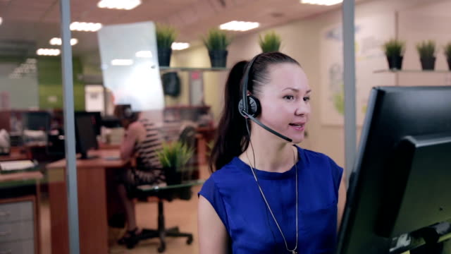 Frendly woman talking on the headset in a bright clean office, call center video