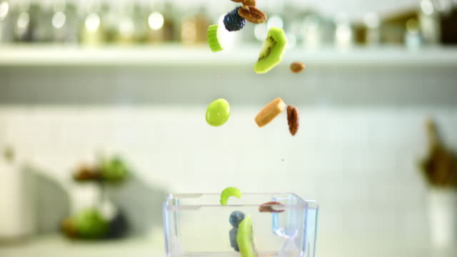 SLO MO fresh and dried fruit flying into a mixer video