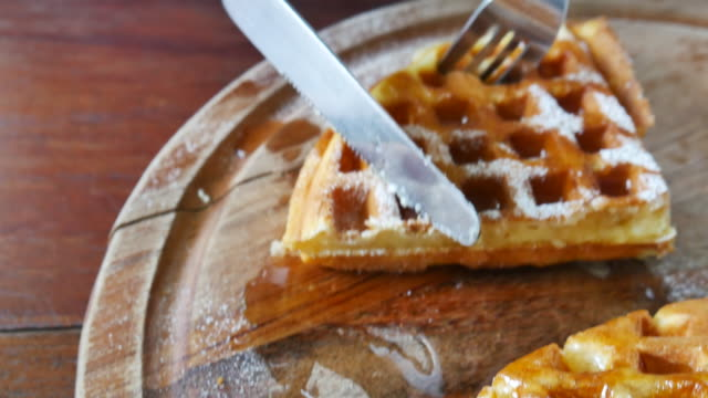 Fresh baked waffle topped with honey syrup is cut into smaller pieces video