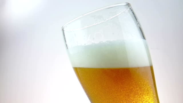 fresh beer with foam into drink pint glass with ice frozen drops, shot slow motion on white background, fun and nutrition food and drink video