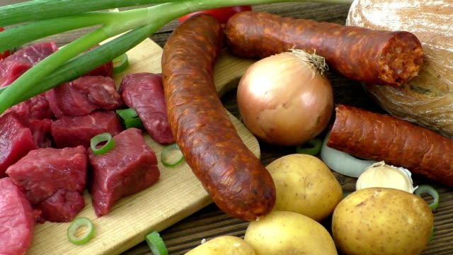 Fresh butcher cut meat assortment garnished on wooden rustic background. video