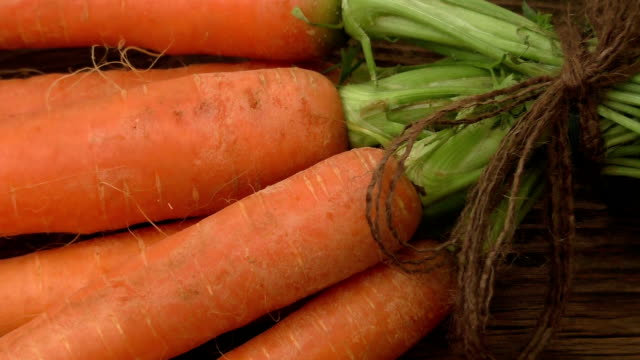 Fresh carrots bunch on rustic wooden background video