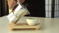 Fresh coffee pouring from mokapot into cup. video