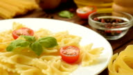 Fresh cooked farfalle with cut tomatoes and basil video