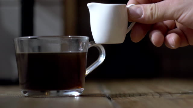 fresh cream poured into a black strong coffee. dark atmospheric cafes, Sunny afternoon video