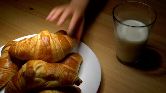 Fresh croissants and milk on wooden table. Children's hand takes the croissant from the plate. video
