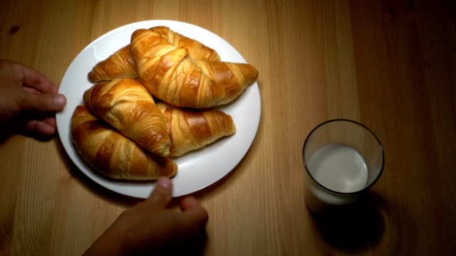 Fresh croissants and milk on wooden table. video