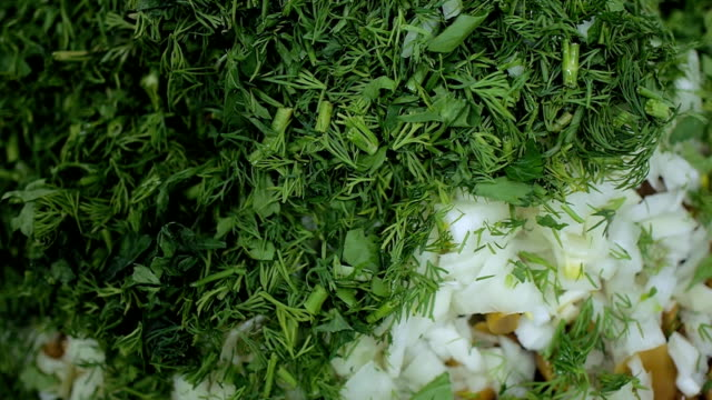 fresh green dill and parsley closeup finely chopped and sprinkled on salad vegetables video