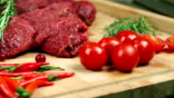 Fresh meat for steak on wooden Board. Marbled meat, beef. Near tomatoes, rosemary, thyme, lemon, red pepper, cranberry. The cook pours the cranberry on the Board, adds rosemary to the meat. video