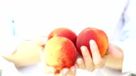 Fresh peaches in woman's hand. video