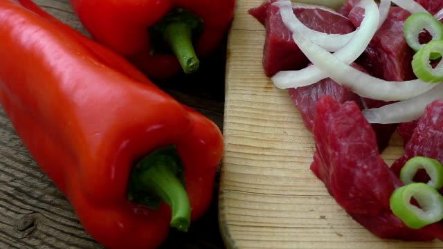 Fresh raw chopped beef on a wooden cutting board with fresh organic vegetables, onion, garlic. video