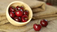Fresh red cherries with water drops on wooden table video