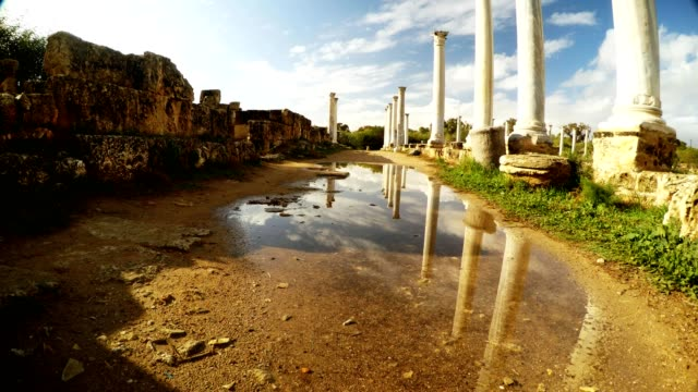 Fresh Spring view Colonnade of Roman Agora reflections of columns blue sky and clouds in puddle antique town Salamis video