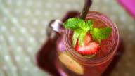 Fresh summer drink red strawberry, lemon and mint serve in mason jar video