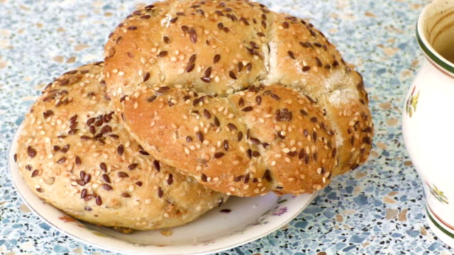 Fresh tasty baked buns with sesame on plate video
