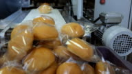 Freshly baked rolls are packed in transparent film, formed a mountain on a conveyor belt video