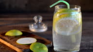 Freshly made lemonade with citrus in a jar and a straw. Dark wooden background, selective focus video