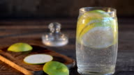 Freshly made lemonade with citrus in the Bank. Dark wooden background, selective focus video