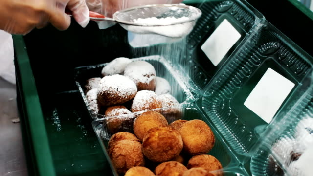 Fried donut sprinkled with white sugar powder. Sweet tooth. Delicious pastries. Production of donuts and packaging video
