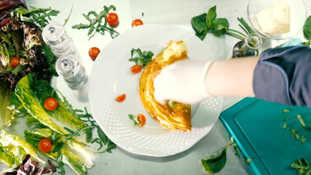Fried eggs on a plate are decorated with tomatoes and herbs with spices video