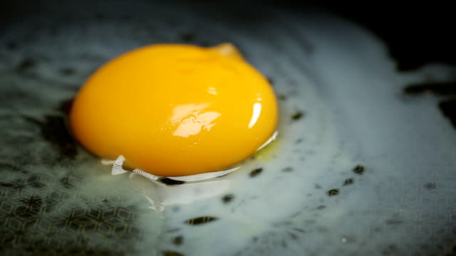 Fried eggs on ceramic frying pan with oil FullHD footage video