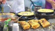 Fried seafood and mussel roll egg pancakes in hot plate, Thai street food video