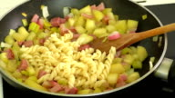 Fried vegetables,pasta,ham in a pan video