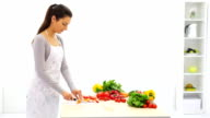Friedly woman in kitchen cutting vegetables. video