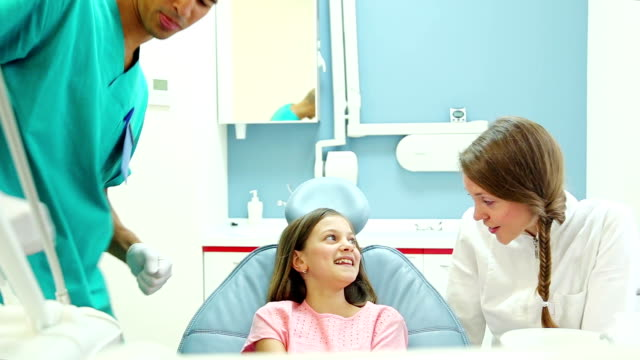 Friendly dentist talks with young patient while assistant examines her video