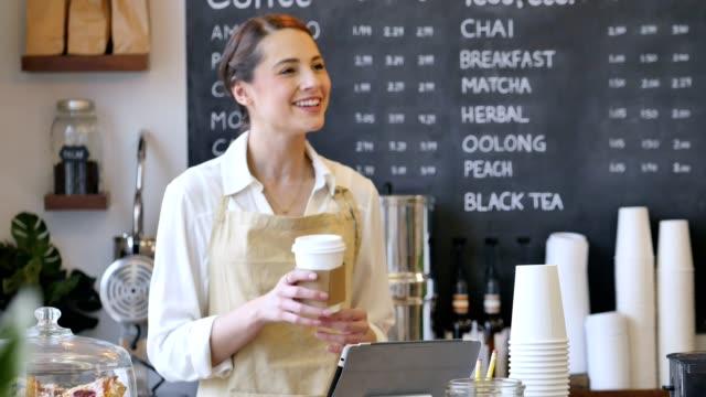 Friendly female barista fills a male customer's order video