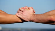 Friendly handshake of two unrecognizable muscular white men on blue sky background. Shaking of male arms outdoor. Two strong men having firm handshake outside. Teamwork and friendship. Close-up video
