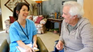 Friendly home healthcare nurse examining senior male patient in assisted living facility video