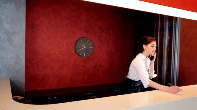 Friendly hotel receptionist meeting newcomers. 4K. video