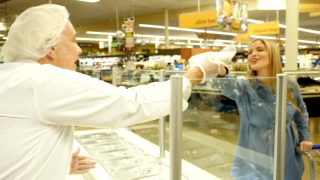 Friendly senior Caucasian deli counter manager or employee hands mid-adult Caucasian female customer her deli order video