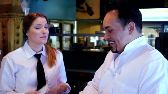 Friendly waitress being trained by Hispanic chef in casual restaurant video