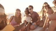 Friends at a sunset beachparty with a guitar video
