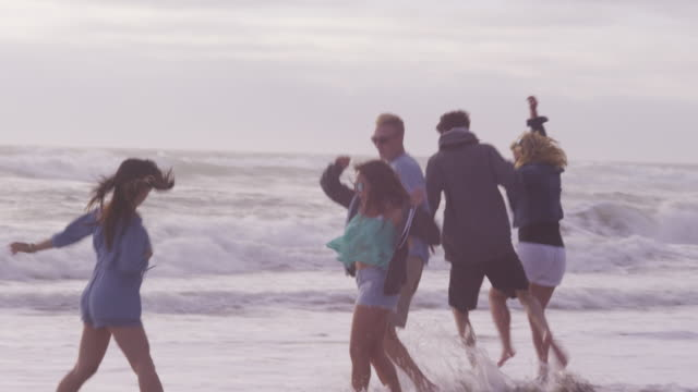 Friends at beach running together video