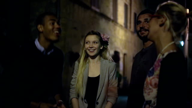 Friends chattering at night in old town centre video HD video