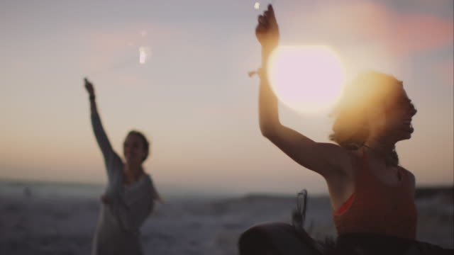 Friends dacing around with sparklers at the beach video