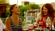 Friends dining on rooftop deck of building video
